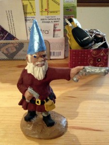 Zombies beware! This gun-wielding gnome just got a little more dangerous with a 'stache and matching satchel.